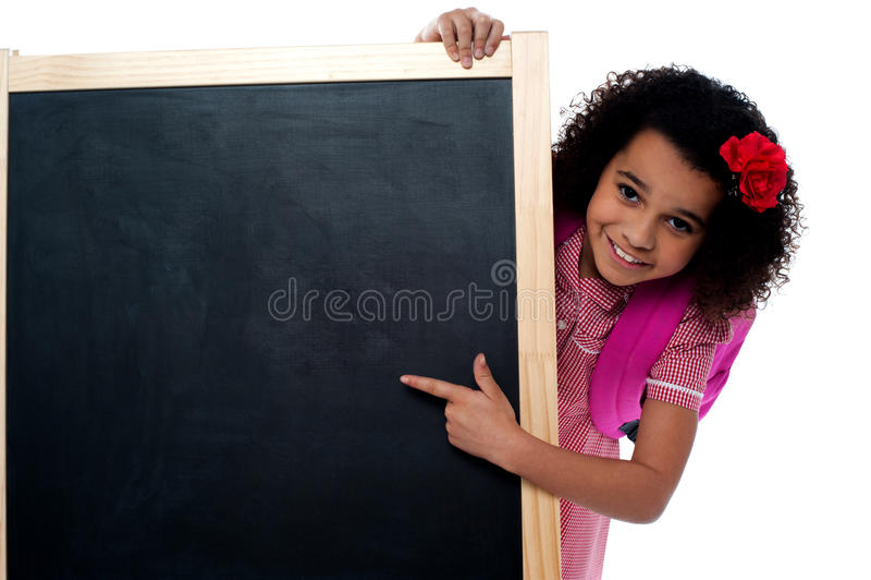 A menina de sorriso olha atrás da placa ereta foto de stock royalty free