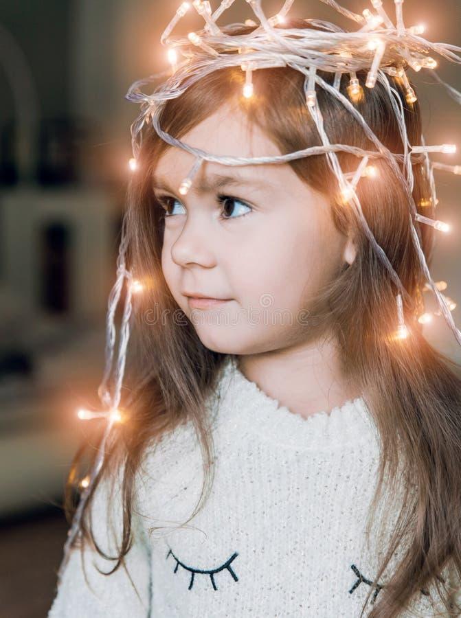 Menina de sorriso pequena bonito com a festão luminosa do Natal em sua cabeça  fotos de stock