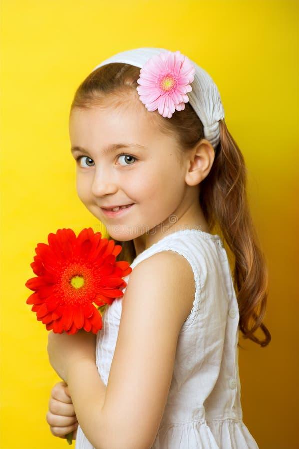 Menina de sorriso pequena com flores fotografia de stock royalty free