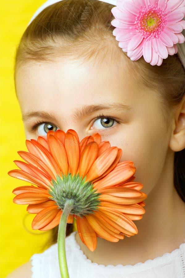 Menina de sorriso pequena com flores fotos de stock royalty free
