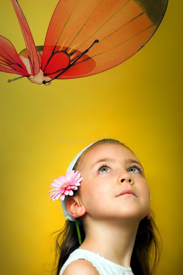 Menina de sorriso pequena com uma borboleta fotografia de stock