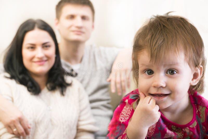 Menina de sorriso pequena da criança com os pais na distância imagens de stock