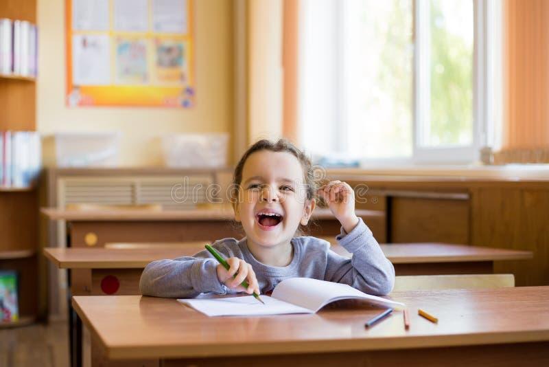 A menina de sorriso pequena feliz que senta-se na mesa na sala de classe e come?a a tirar com cuidado em um caderno puro Aluno fe imagem de stock
