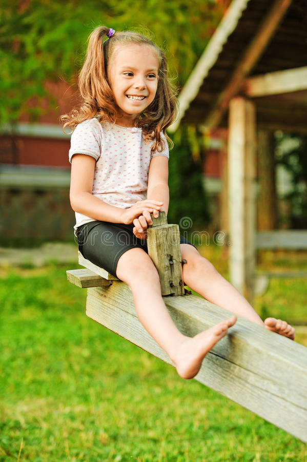 Menina de sorriso pequena no balanço fotografia de stock royalty free