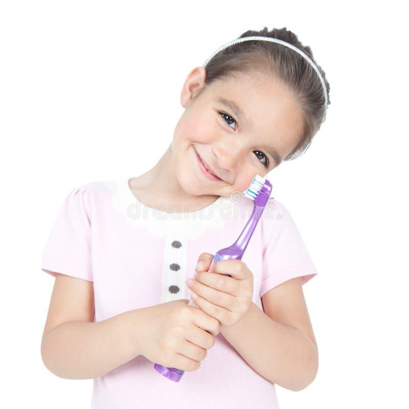 Menina de sorriso pequena que guardara uma escova de dentes fotografia de stock royalty free