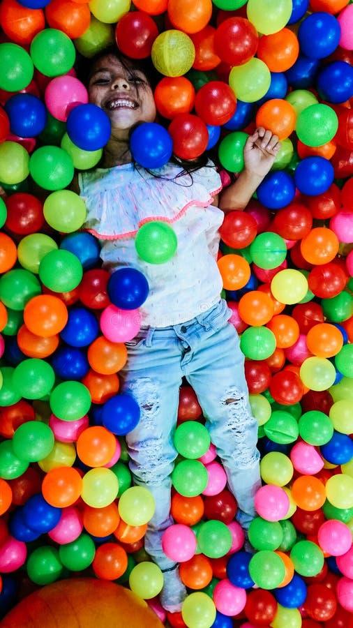 Menina de sorriso pequena que joga o encontro em bolas coloridas imagem de stock
