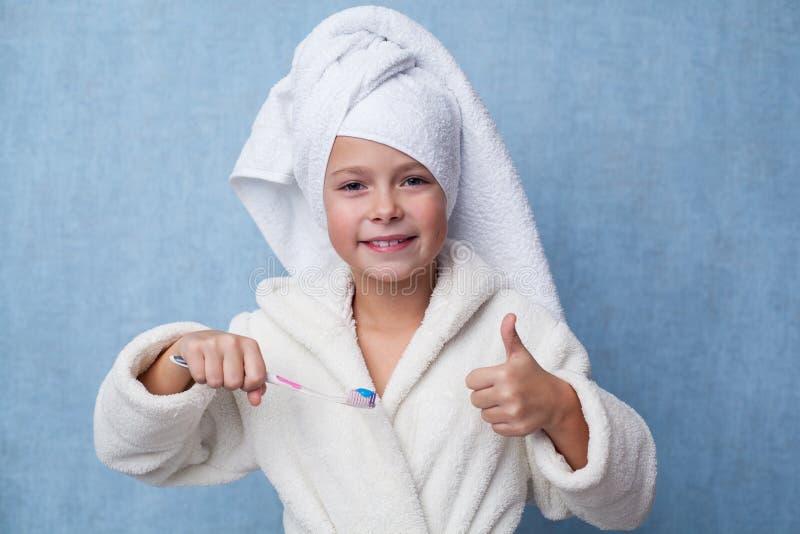 Menina de sorriso pequena que prende um toothbrush foto de stock