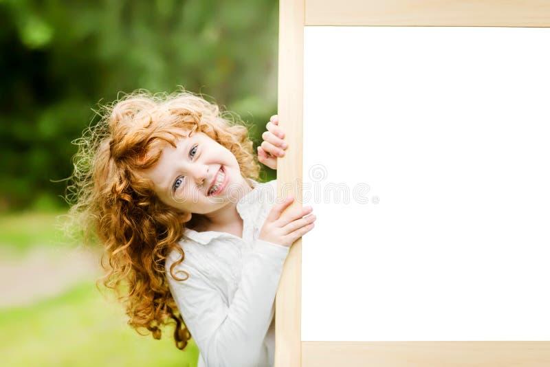 Menina de sorriso perto de uma placa branca Conceito educacional e médico imagem de stock royalty free