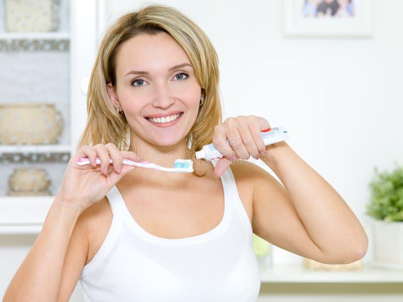 A menina de sorriso prende o toothbrush com um dentífrico fotos de stock royalty free