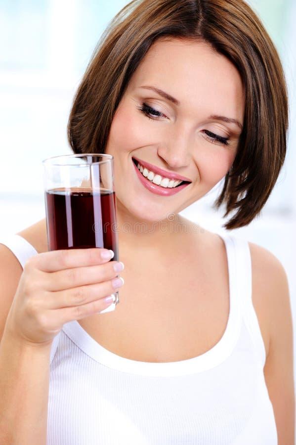 A menina de sorriso prende um vidro do suco da romã imagens de stock royalty free