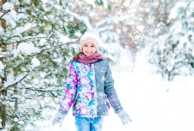 Menina de sorriso que anda na floresta do inverno imagem de stock