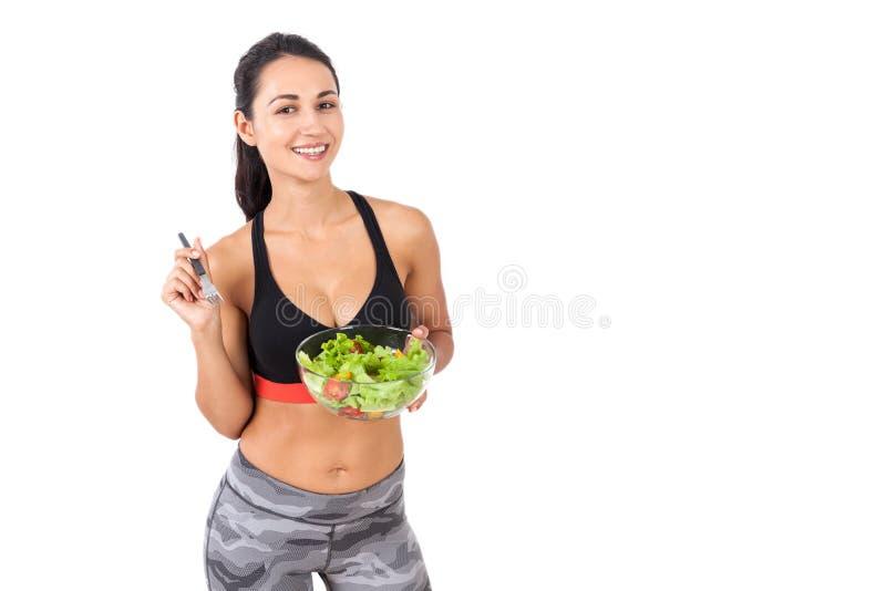 Menina de sorriso que come felizmente sua salada imagens de stock