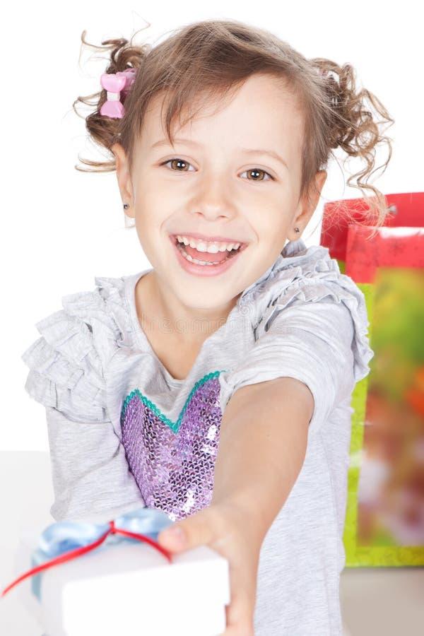 Menina de sorriso que dá lhe um presente no estúdio imagem de stock royalty free