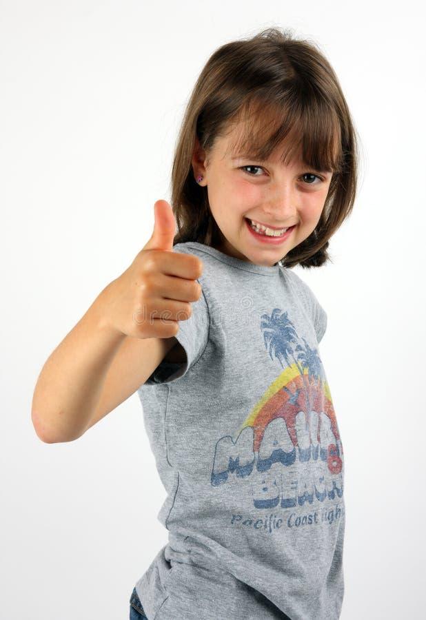 Menina de sorriso que dá os polegares acima fotos de stock