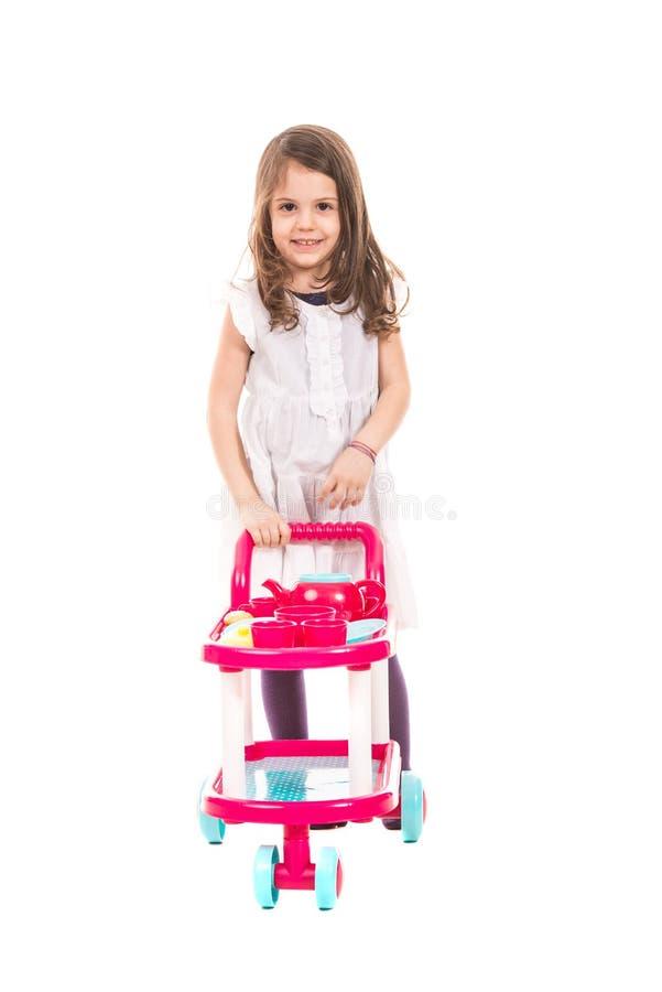 Menina de sorriso que empurra o brinquedo do pram fotografia de stock