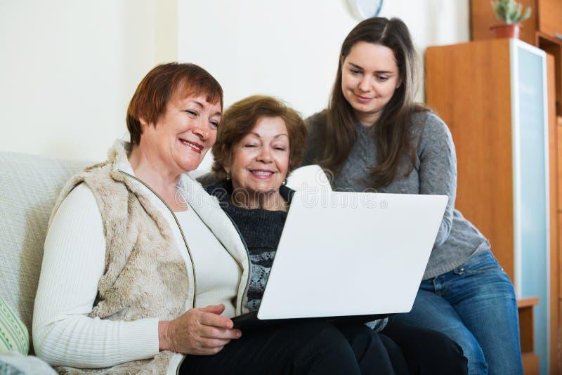 Menina de sorriso que ensina as mulheres superiores positivas que usam o portátil fotos de stock royalty free