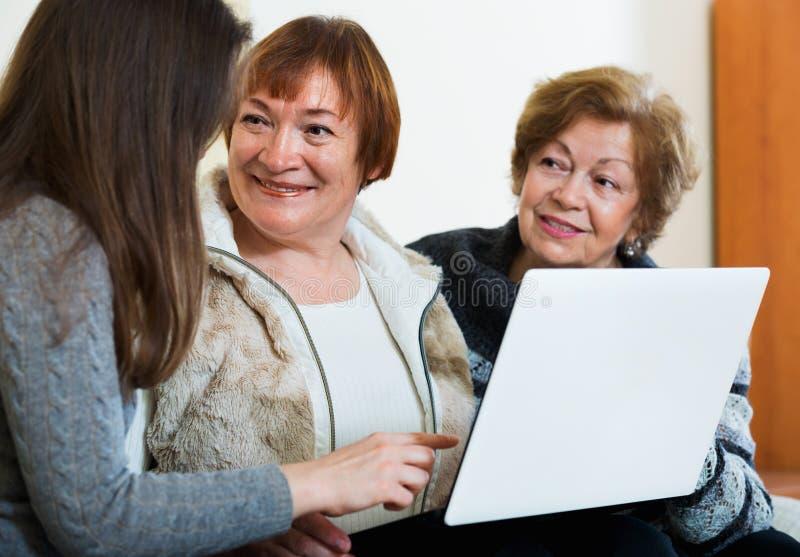 Menina de sorriso que ensina as mulheres superiores positivas que usam o portátil imagem de stock