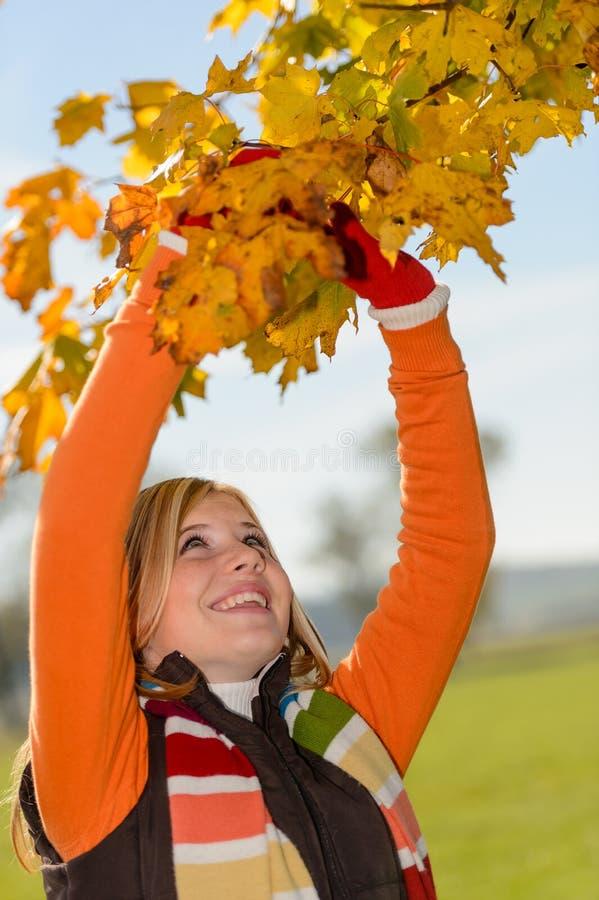 Menina de sorriso que escolhe a árvore seca do outono das folhas foto de stock