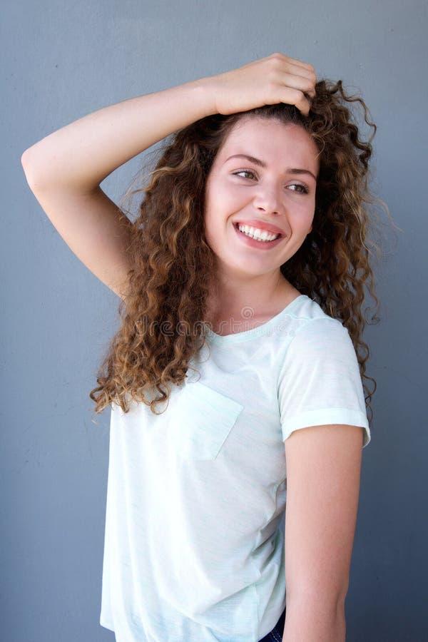 Menina de sorriso que está com mão no cabelo fotografia de stock royalty free