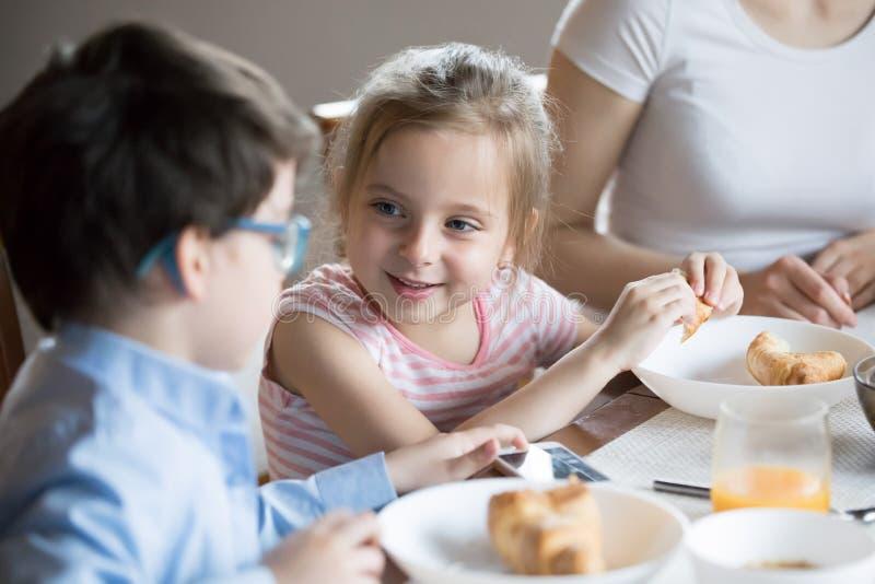 Menina de sorriso que fala com o irmão no café da manhã em casa foto de stock royalty free