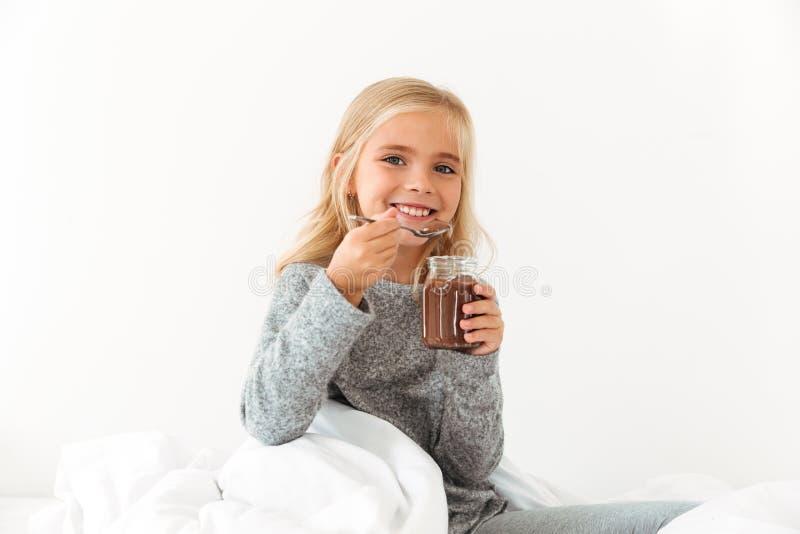 Menina de sorriso que guarda o banco do spr da avelã do chocolate doce foto de stock
