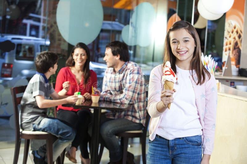 Menina de sorriso que guarda o cone do creme de Vanilla Ice na sala de estar imagem de stock