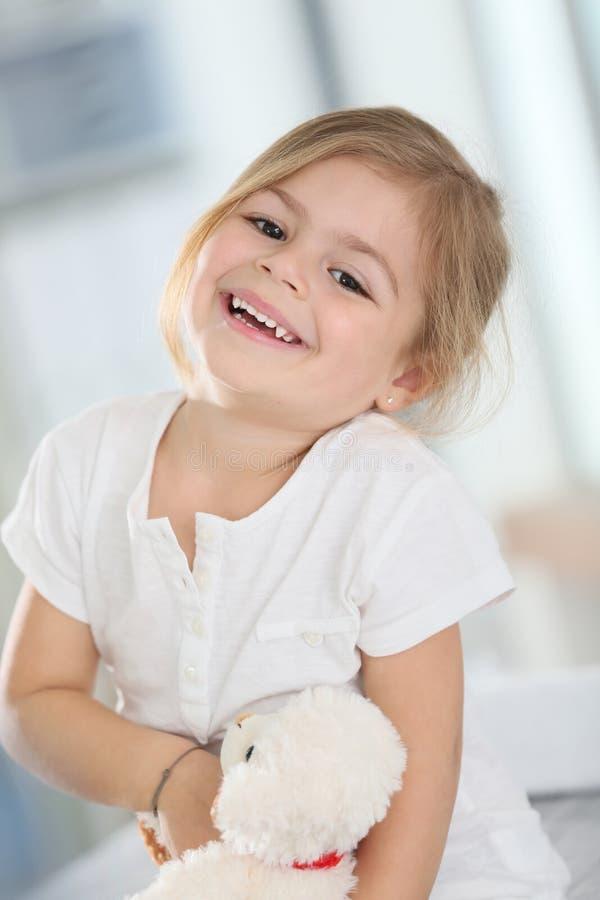 Menina de sorriso que guarda o urso de peluche fotografia de stock royalty free