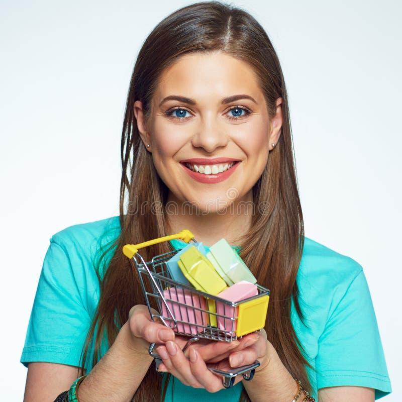 Menina de sorriso que guarda pouco carro do mercado com muitas caixas de presente diminutas imagem de stock