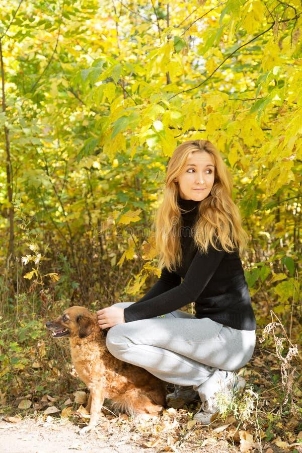 A menina de sorriso que guarda um cão vermelho no outono estaciona fotografia de stock royalty free