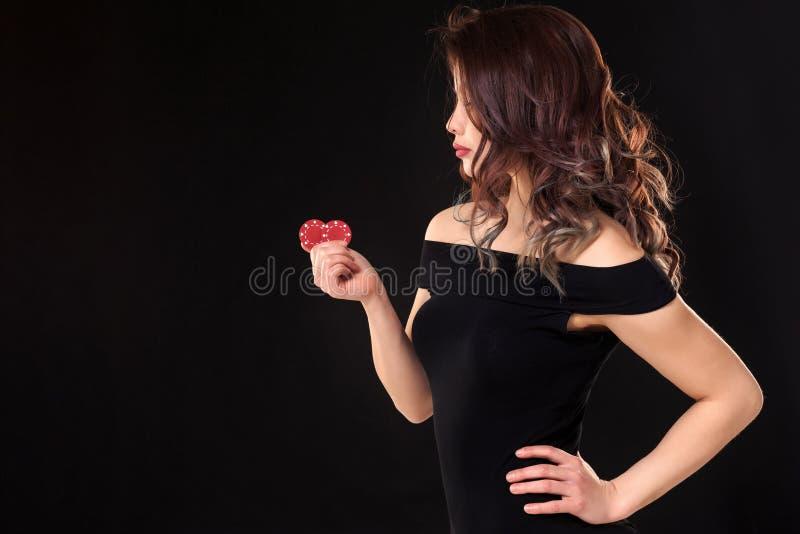 A menina de sorriso que guarda um jogo lasca-se em suas mãos no fundo preto Copie o espaço fotografia de stock