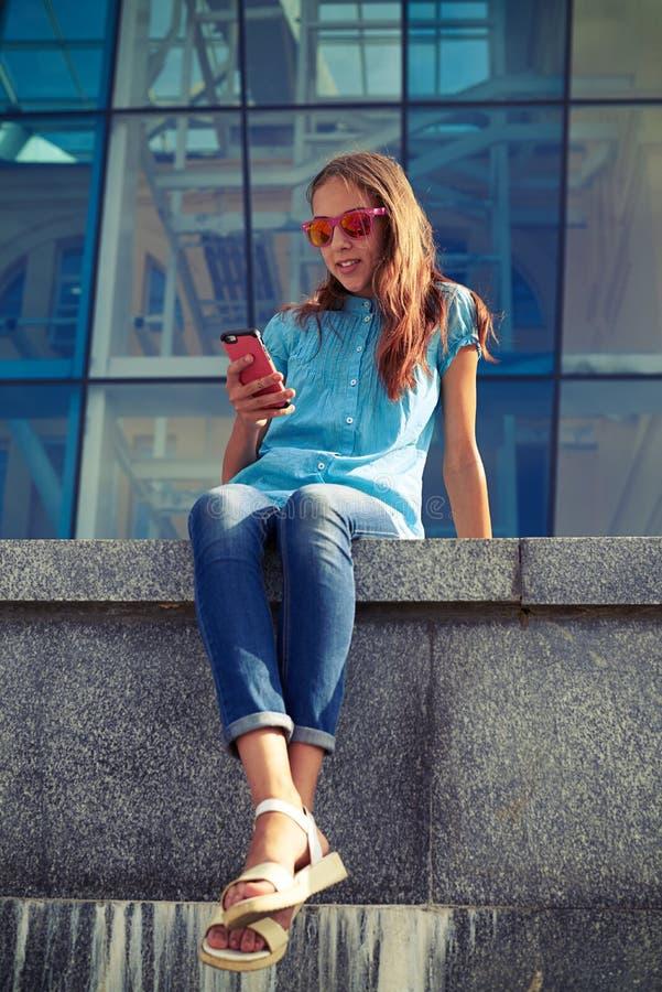 Menina de sorriso que guarda um telefone ao sentar-se no banco concreto foto de stock royalty free