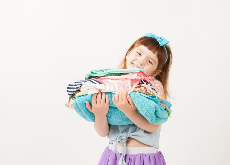 Menina de sorriso que guarda uma pilha de roupa dobrada fotos de stock royalty free