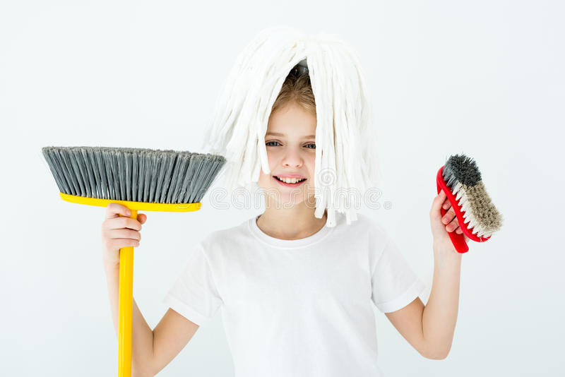 Menina de sorriso que guarda várias fontes de limpeza no branco fotografia de stock