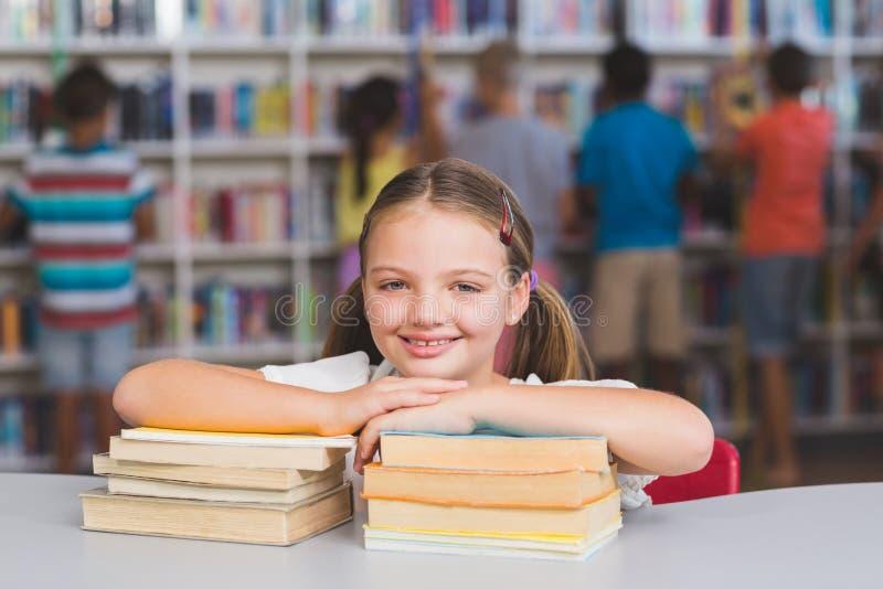 Menina de sorriso que inclina-se na pilha dos livros na biblioteca fotografia de stock royalty free