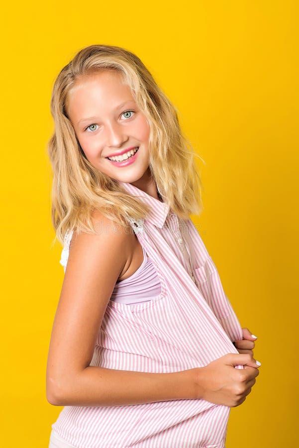 Menina de sorriso que levanta no fundo amarelo Felicidade, atividade e conceito da crian?a Inf?ncia feliz e saud?vel Menina da es fotos de stock