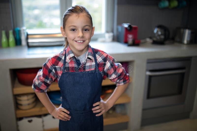 Menina de sorriso que levanta vestindo um avental na cozinha fotos de stock royalty free