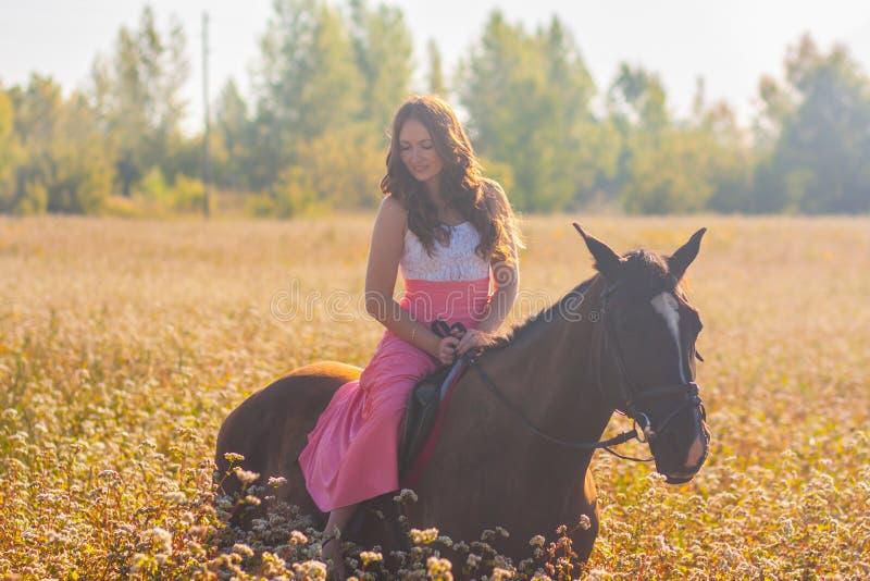 menina de sorriso que monta um cavalo preto em um vestido cor-de-rosa fotografia de stock royalty free