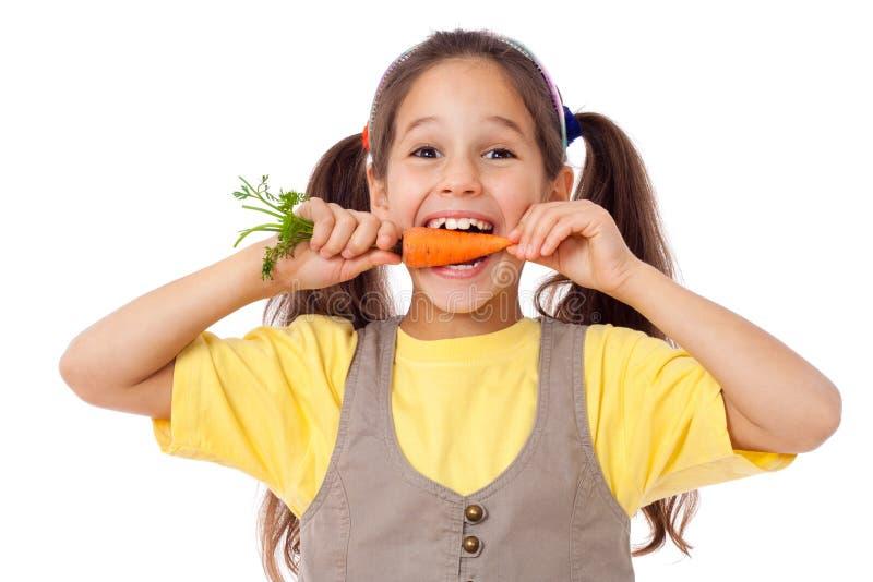 Menina de sorriso que morde a cenoura fotografia de stock royalty free
