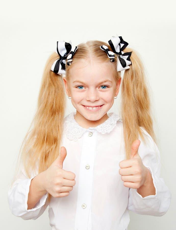 A menina de sorriso que mostra os polegares levanta o símbolo fotografia de stock