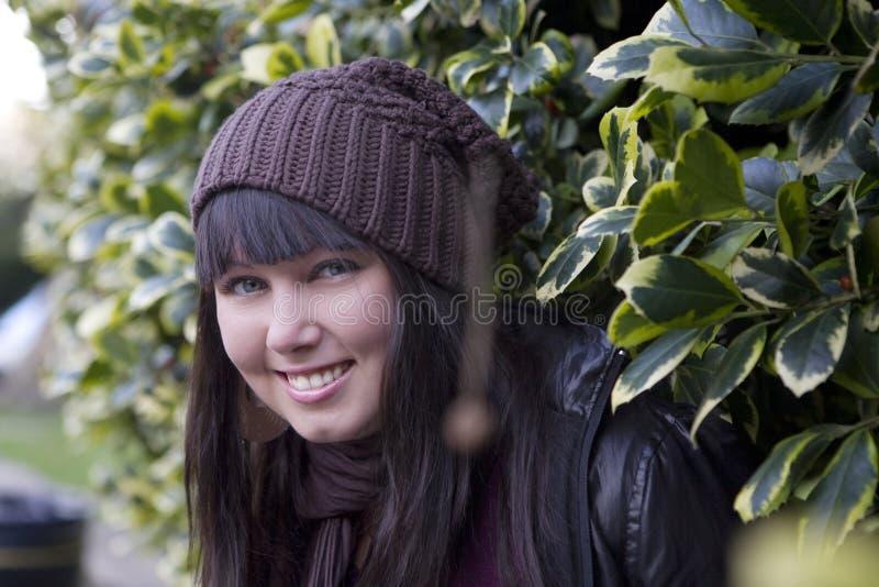 Menina de sorriso que olha do arbusto verde foto de stock