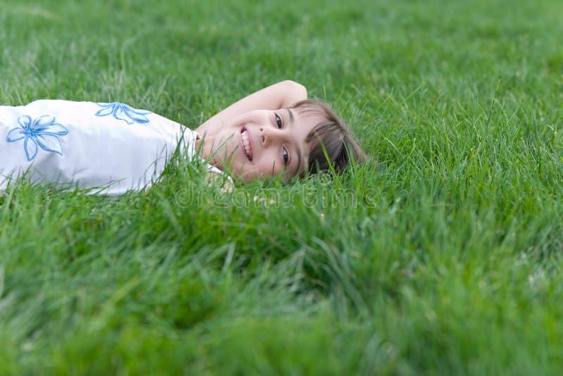 Menina de sorriso que olha fora da grama verde foto de stock royalty free