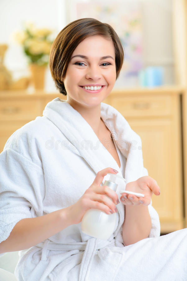 Menina de sorriso que põe cosméticos sobre a almofada de algodão imagens de stock