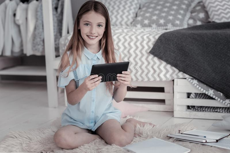 Menina de sorriso que senta-se com uma tabuleta foto de stock royalty free