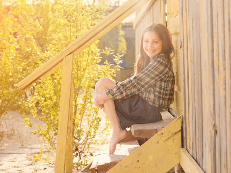 Menina de sorriso que senta-se em escadas de madeira com os pés descalços fotografia de stock royalty free