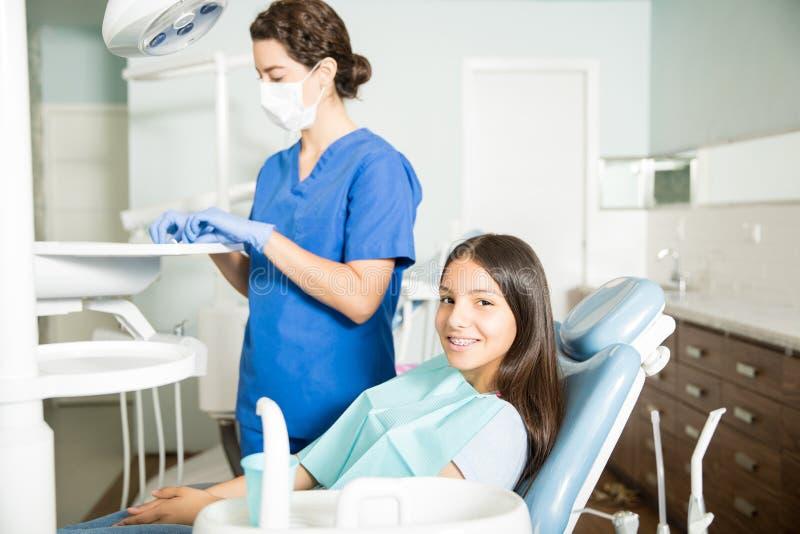 Menina de sorriso que senta-se na cadeira quando dentista Working In Clinic imagens de stock royalty free