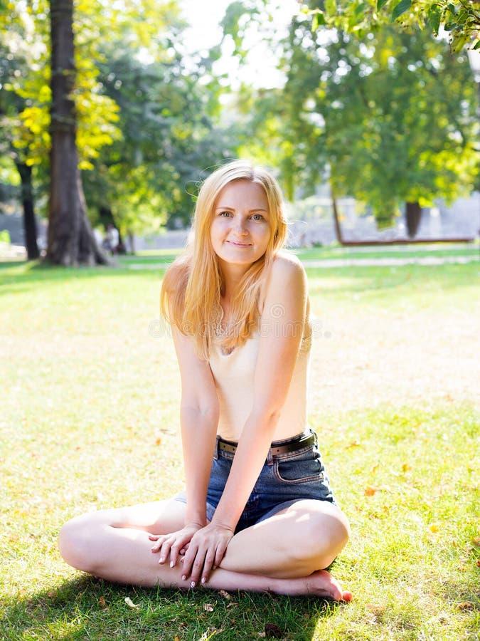 Menina de sorriso que senta-se na grama verde fora olhando a câmera Exterior na natureza fotografia de stock royalty free