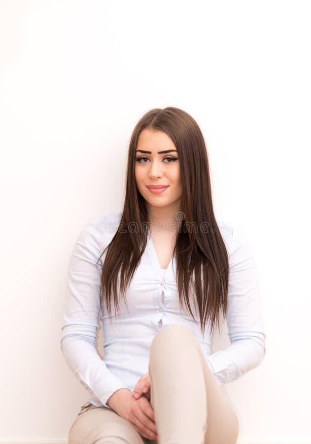 Menina de sorriso que senta-se no assoalho fotos de stock