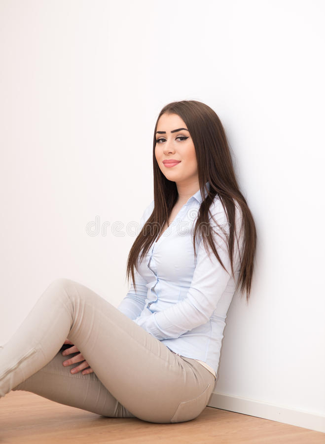 Menina de sorriso que senta-se no assoalho fotos de stock royalty free