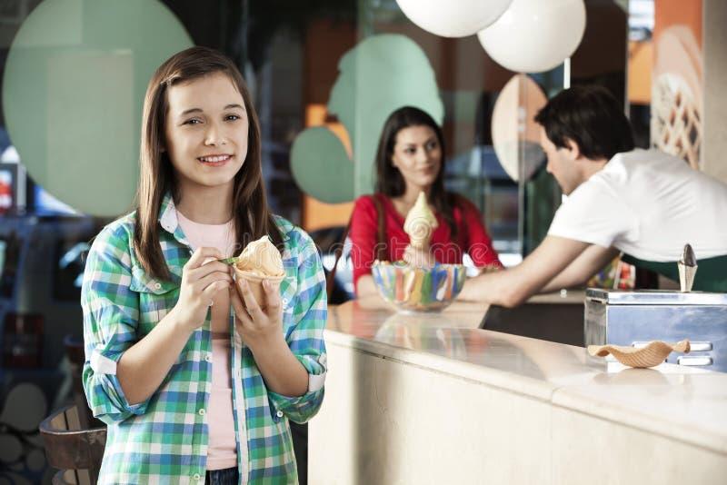 Menina de sorriso que tem o gelado na sala de estar fotos de stock royalty free