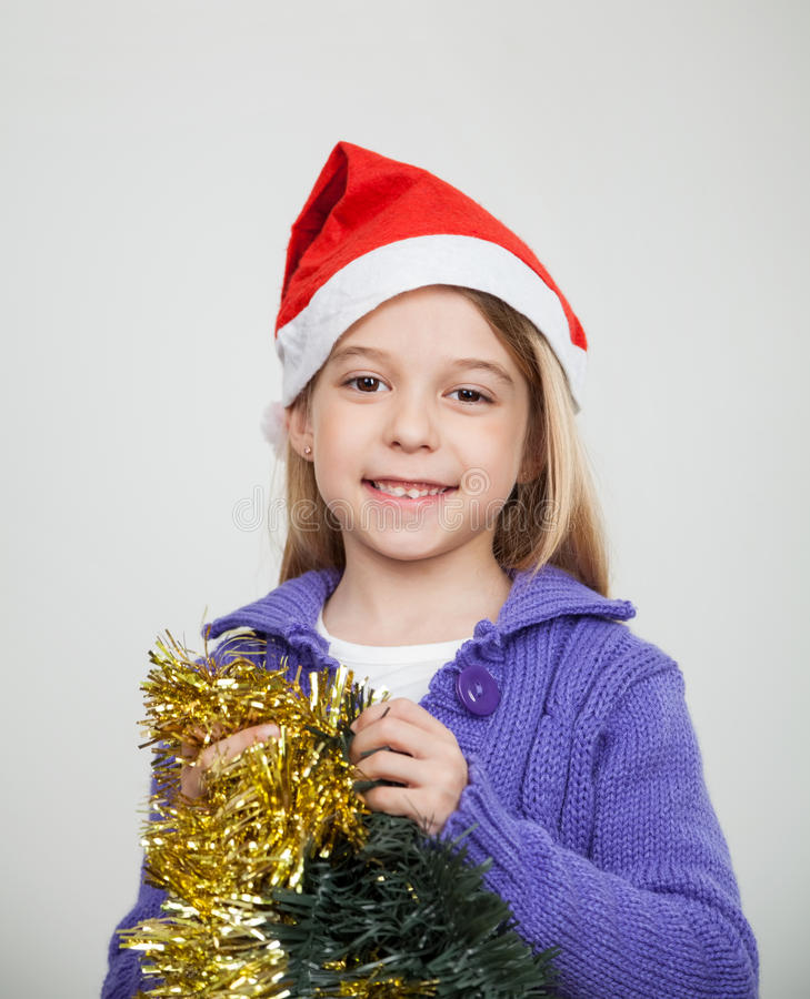 Menina de sorriso que veste Santa Hat Holding Tinsels imagens de stock